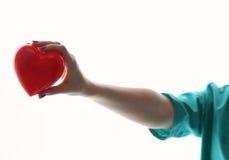Medico con lo stetoscopio che esamina cuore rosso Immagine Stock