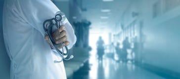 Medico con lo stetoscopio a disposizione sul fondo dell'ospedale fotografie stock libere da diritti