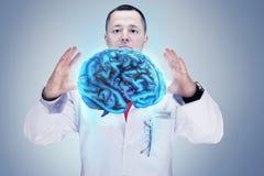 Medico con lo stetoscopio e cervelli sulle mani Fondo grigio Di alta risoluzione immagini stock
