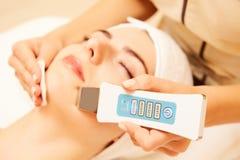 Medico con scraber ultrasonico Fare procedura di pulizia ultrasonica del fronte Modello, profilo Clinica di Cosmetological fotografia stock
