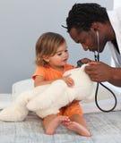 Medico con un bambino in un ospedale Immagini Stock