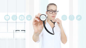 Medico con uno stetoscopio nelle mani e nelle icone mediche Fotografia Stock