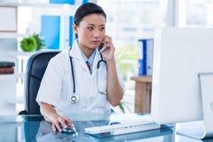 Medico concentrato che ha telefonata e che per mezzo del suo computer fotografia stock