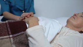 Medico curante che segna mano del paziente femminile, sostenente la, centro ospedaliero archivi video