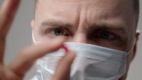Medico dei giovani nella maschera esamina una pillola stock footage