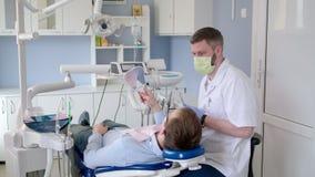Medico del dentista durante la visita di consultazione nella clinica di stomatologia di sanità stock footage