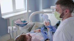 Medico del dentista sta consultando l'uomo paziente nella clinica della stomatologia stock footage