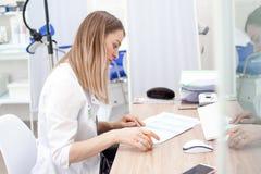 Medico del ginecologo in uniforme bianca negli impianti dell'ospedale della clinica sul computer Gabinetto ginecologico con la se fotografia stock