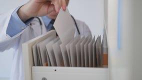 Medico del movimento lento nell'ufficio dell'ospedale apre un cassetto che cerca le cartelle sanitarie video d archivio