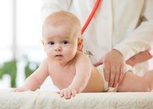 Medico del pediatra esamina il bambino con lo stetoscopio che controlla il battito cardiaco immagini stock libere da diritti