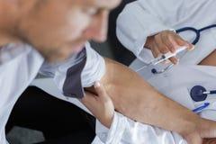 Medico del primo piano che inietta paziente con la siringa per raccogliere sangue Fotografia Stock Libera da Diritti