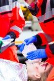 Medico dell'ambulanza che dà ossigeno alla vittima femminile Immagine Stock