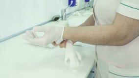 Medico dell'uomo mette sopra i guanti sterili che stanno nel dipartimento di traumatologia stock footage