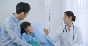 Medico della donna che esamina termometro dopo la misura di temperatura video d archivio