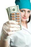 Medico della donna che mostra soldi ed i ridurre in pani Fotografie Stock