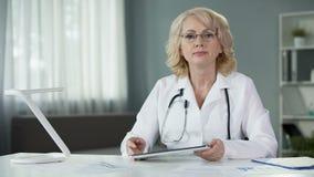 Medico della donna che tiene consultazione online del paziente che usando le tecnologie moderne stock footage