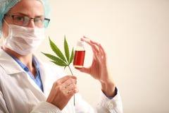 Medico della donna che tiene una cannabis copre di foglie e lubrifica Medicina alternativa fotografie stock