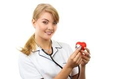 Medico della donna con lo stetoscopio che esamina cuore rosso, concetto di sanità Fotografie Stock Libere da Diritti