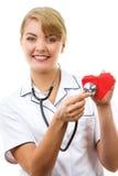 Medico della donna con lo stetoscopio che esamina cuore rosso, concetto di sanità Immagini Stock Libere da Diritti