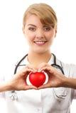 Medico della donna con lo stetoscopio che tiene cuore rosso, concetto di sanità Immagini Stock Libere da Diritti