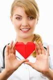 Medico della donna con lo stetoscopio che tiene cuore rosso, concetto di sanità Fotografie Stock