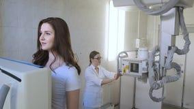 Medico della donna conduce la macchina di raggi x medica nel laboratorio diagnostico dell'ospedale per la ragazza stock footage