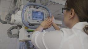 Medico della donna conduce la macchina di raggi x medica nel laboratorio diagnostico dell'ospedale per la ragazza video d archivio