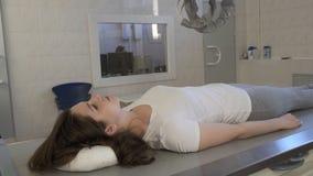 Medico della donna conduce la macchina di raggi x medica nel laboratorio diagnostico dell'ospedale per la ragazza archivi video