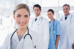 Medico della donna davanti ai suoi colleghi Immagine Stock Libera da Diritti