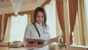 Medico della ragazza che cammina nell'ospedale con i documenti stock footage