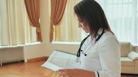 Medico della ragazza che cammina nell'ospedale con i documenti Fotografie Stock