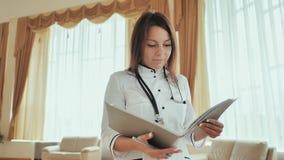 Medico della ragazza che cammina nell'ospedale con i documenti Immagine Stock