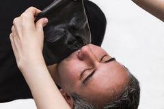 Medico di bellezza rimuove la maschera del nero dell'alga dell'alginato della pelle dal fronte paziente maschio Immagini Stock Libere da Diritti