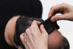 Medico di bellezza rimuove la maschera del nero dell'alga dell'alginato della pelle dal fronte paziente maschio Immagine Stock