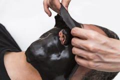 Medico di bellezza rimuove la maschera del nero dell'alga dell'alginato della pelle dal fronte paziente maschio Immagine Stock Libera da Diritti