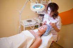Medico di cosmetologia che mette una donna sulla crema di fronte fotografie stock libere da diritti
