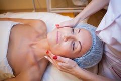 Medico di cosmetologia fa il massaggio del facial dei trattamenti della donna fotografia stock