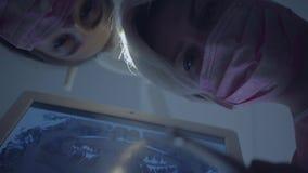 Medico di due abilità si è piegato sopra un paziente non riconosciuto pronto per il trattamento dentario Trattamento dentario, co video d archivio