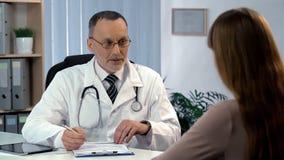 Medico di famiglia che ascolta il paziente, compilante assicurazione-malattia, sanità fotografie stock libere da diritti