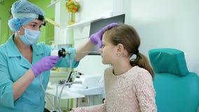 Medico di Lor cura un bambino malato, un apparato per il trattamento di angina, il trattamento della clinica del ` s dei bambini  stock footage