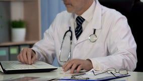 Medico di medicina che scrive articolo scientifico per la rivista, lavorante al computer portatile immagine stock libera da diritti