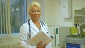 Medico di mezza età della donna con lo stetoscopio sta in reparto video d archivio