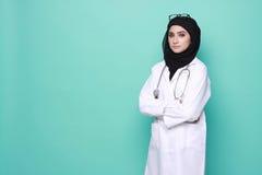 Medico di Muslimah isolato nel fondo del turchese Immagini Stock