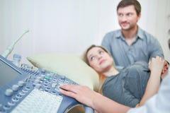 Medico di partecipazione amoroso delle coppie per il procedu del suono di gravidanza ultra fotografia stock libera da diritti
