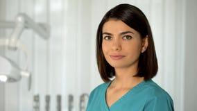 Medico di signora con il sorriso incantante che posa per la fiducia e la professionalità della macchina fotografica immagine stock