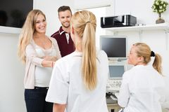 Medico di visita delle coppie in grande aspettativa Fotografia Stock