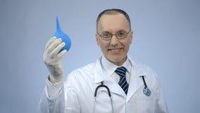 Medico divertente che tiene siringa rettale con il sorriso sul fronte, scherzare del proctologo Fotografie Stock Libere da Diritti