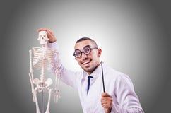 Medico divertente con lo scheletro contro la pendenza Immagine Stock