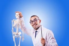Medico divertente con lo scheletro contro la pendenza Fotografie Stock Libere da Diritti