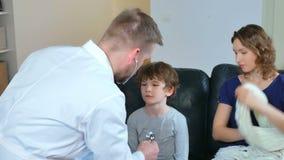Medico domestico è venuto al ragazzo malato ed a sua madre esamina un bambino e registra le letture in taccuino archivi video